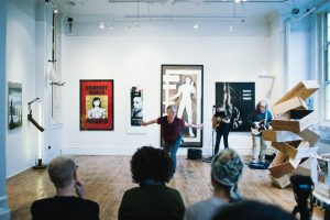 Mark DeGarmo performing for an audience in an art gallery.