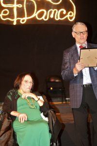 Maxine Green sitting beside a man who is speaking into a microphone and reading from a tablet in his hand.
