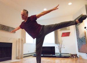 Mark DeGarmo embodying an angular shape with one leg in the air parallel to the ground.