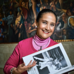Patricia Aulestia smiling for a photo while holding a photo of a dancer.