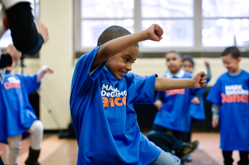 Small child dancing with his arms over head and a smile on his face.