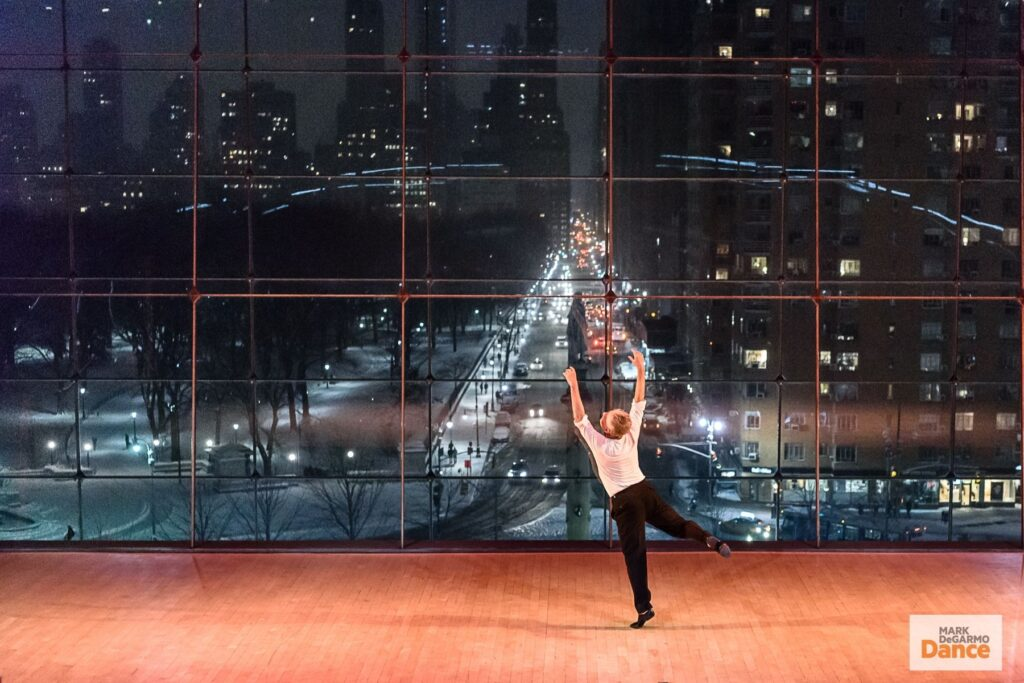 Mark DeGarmo dances with arms and one leg up in at Jazz at Lincoln Center in front of a wall of windows looking out onto NYC
