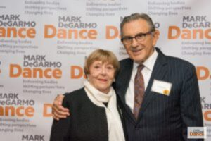 Oleg Briansky and Mireille Briane posing for a photo together in front of an MDD backdrop.