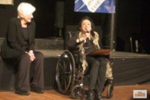 Judith Malina sitting in a wheelchair while speaking into a microphone. Another lady sits beside her watching Malina with a smile.