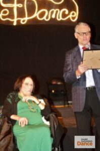 Maxine Green sitting beside a Mark DeGarmo. DeGarmo is speaking into a microphone and reading from a award plaque in his hand.